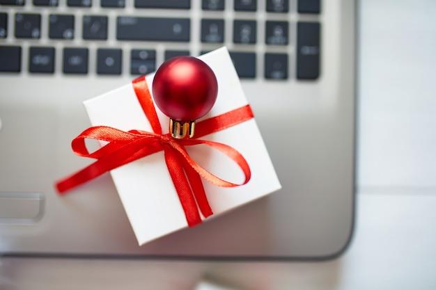 Acquisti online di capodanno e natale a casa, concetto di quaranina, notebook e confezione regalo su fondo di legno bianco, vista dall'alto, spazio di copia