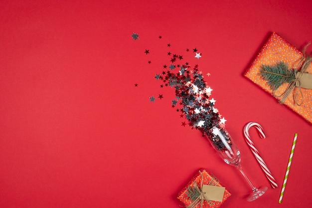 Capodanno e natale sfondo rosso con bicchieri di champagne con coriandoli e scatole regalo laici piatta