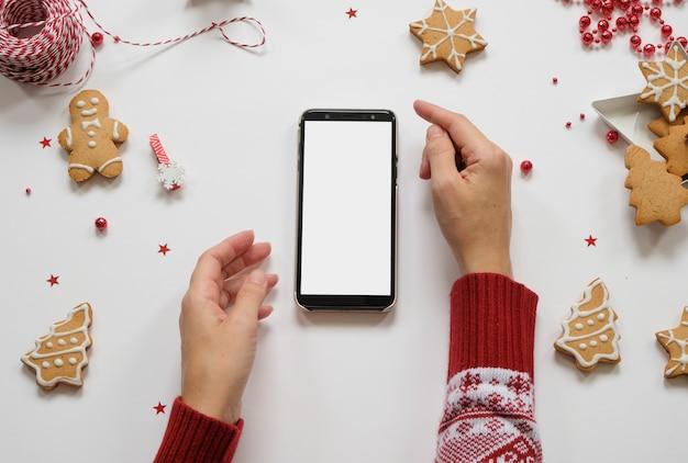Shopping di natale e capodanno. telefono su un tavolo bianco con decorazioni rosse