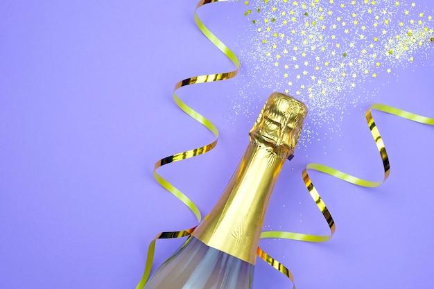 Bottiglia di champagne composizione di capodanno con lustrini e nastri.