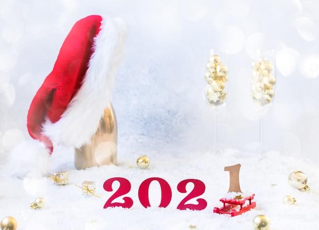 Composizione di capodanno con bottiglia di champagne, numeri 2021 e cappello da babbo natale sul pavimento innevato