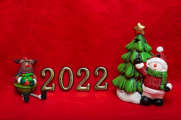 Anno nuovo concetto cervo marrone, pupazzo di neve con abete e numeri d'oro su sfondo rosso. il nuovo anno 2022 sta arrivando. layout da cartolina, confezione. banner