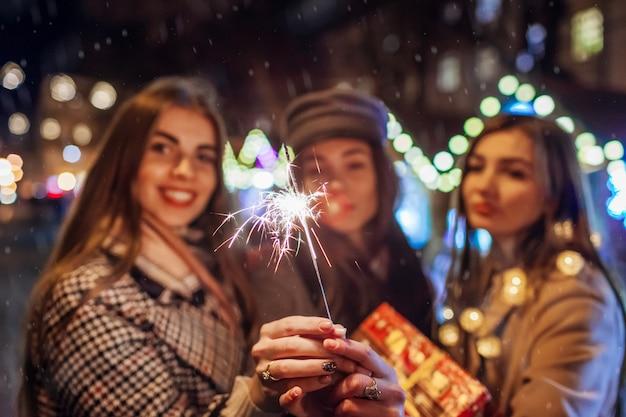 Anno nuovo concetto. amici delle donne che bruciano stelle filanti a lviv sulla fiera di strada divertendosi con i regali. ragazze che celebrano le vacanze sotto la neve