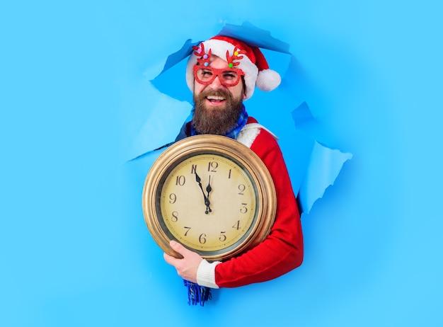 Conto alla rovescia per il nuovo anno tempo per festeggiare tempo per la festa invernale babbo natale sorpreso guarda attraverso la carta h...