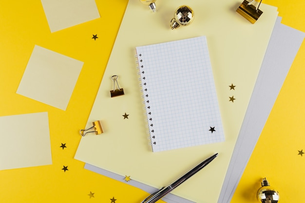 Decorazione del nuovo anno della tabella gialla della scrivania con il taccuino in bianco e altre forniture per ufficio. vista dall'alto con copia spazio, piatto laici.