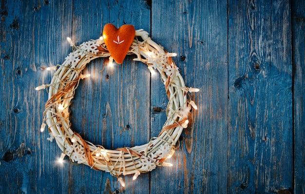 Decorazioni del nuovo anno intorno allo spazio vuoto della lettera di natale per la superficie di legno blu delle ghirlande delle luci brucianti del testo