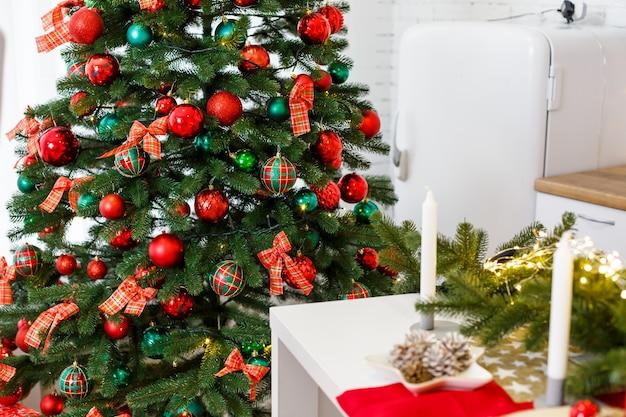 Decorazioni di capodanno in cucina: un albero verde decorato con palline rosse e verdi, decorazioni di capodanno, ghirlande gialle. capodanno. decorare la casa per natale