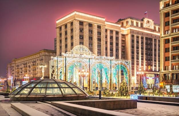 Decorazioni di capodanno in piazza manezhnaya e vicino all'edificio della duma di stato a mosca in una notte d'inverno