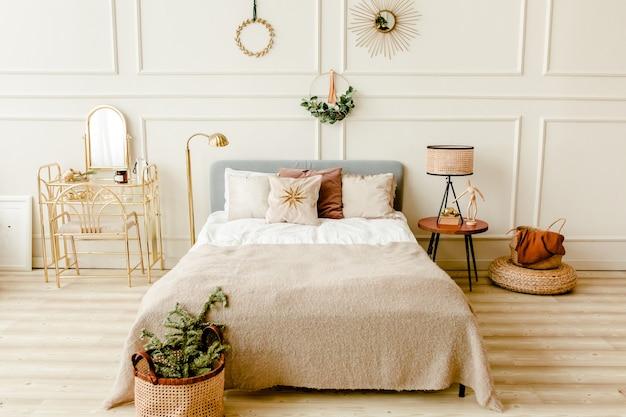Interior design di capodanno della bella camera da letto nei toni del beige con rami di abete ghirlanda