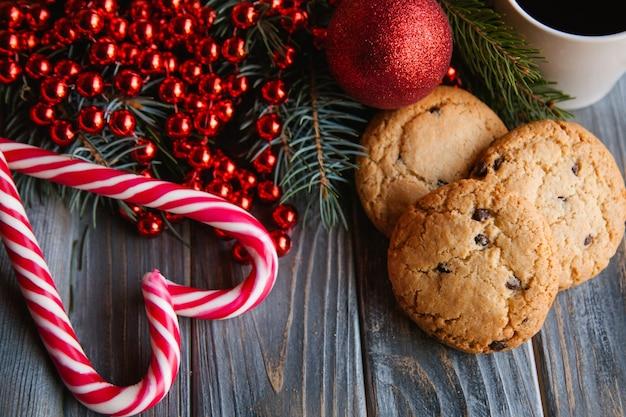 Decorazione festiva del nuovo anno su fondo di legno. biscotti con gocce di cioccolato e bastoncini di zucchero a forma di cuore. concetto di cibi stagionali.