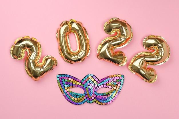 Numeri di palloncini stagnola di nuovo anno su sfondo rosa natale di capodanno