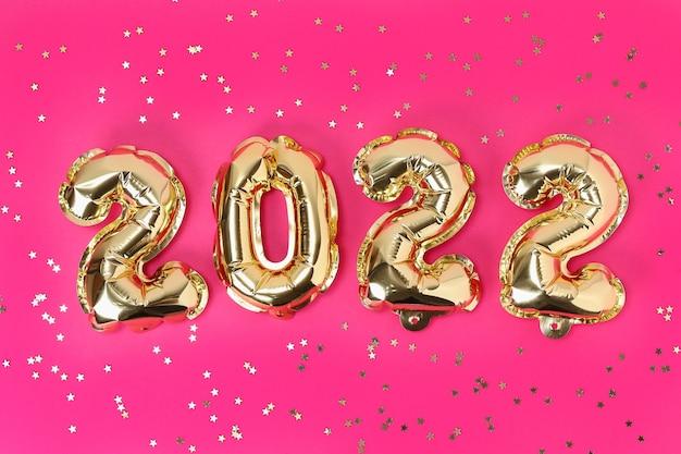 Numeri di palloncini foil di capodanno su sfondo rosa