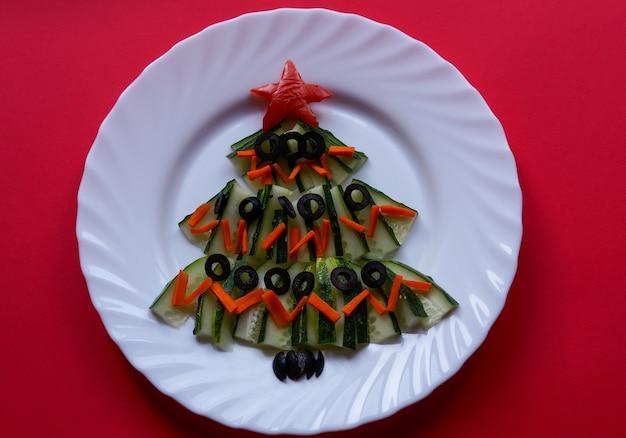 Cibo di capodanno albero di natale fatto di cibo su uno sfondo rosso idea creativa di capodanno