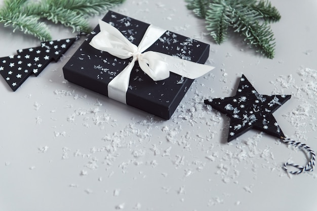 Confezione regalo di capodanno nastro bianco neve e rami di albero di natale sfondo grigio