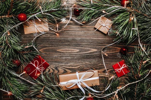 Regali di capodanno su fondo in legno con albero di natale e giocattoli