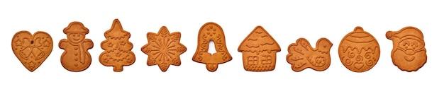 Pan di zenzero di capodanno o cuore, pupazzo di neve, fiocco di neve dell'albero di natale, campana, casetta, uccello, palla e biscotti di babbo natale isolati sul tavolo bianco
