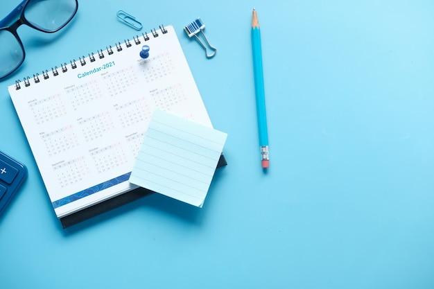 Concetto di obiettivi del nuovo anno con il calendario 2021 su sfondo colorato.