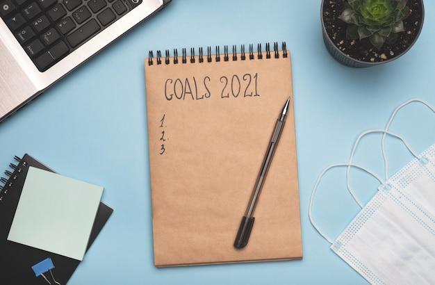 Blocco note degli obiettivi del nuovo anno sulla scrivania dell'ufficio domestico
