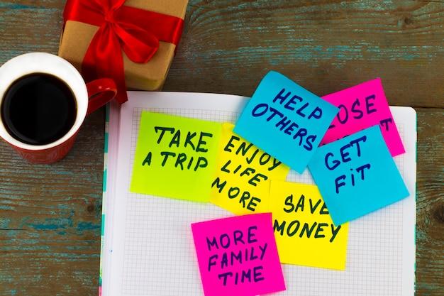 Obiettivi o risoluzioni del nuovo anno - note adesive colorate su un blocco note con una tazza di caffè.