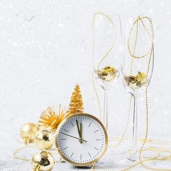 Nuovo anno. decorazione in oro con orologio, palline, albero e coppe in vetro