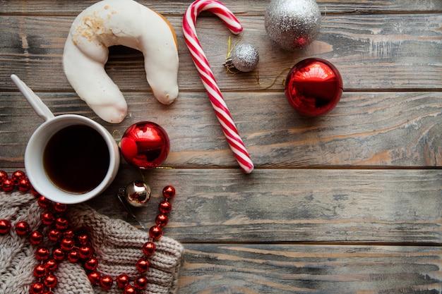 Decorazioni per le vacanze di capodanno su fondo di legno. ornamenti e accessori stagionali. tazza di caffè croissant bastoncino di zucchero perline scintillanti e assortimento di palline. accogliente concetto di umore invernale.