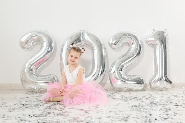 Anno nuovo, vacanze e concetto di celebrazione - bambina bambino seduto vicino con numeri palloncini 2021