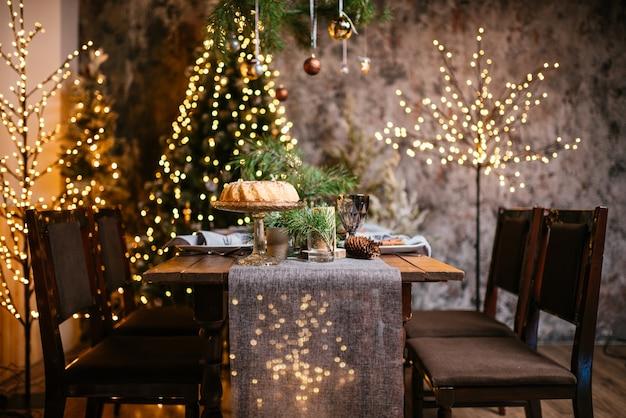Interno di capodanno con lampadine candele e bokeh camera decorata per la celebrazione del natale albero di natale con regali