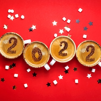 Il nuovo anno è disegnato su tazze di caffè su sfondo rosso