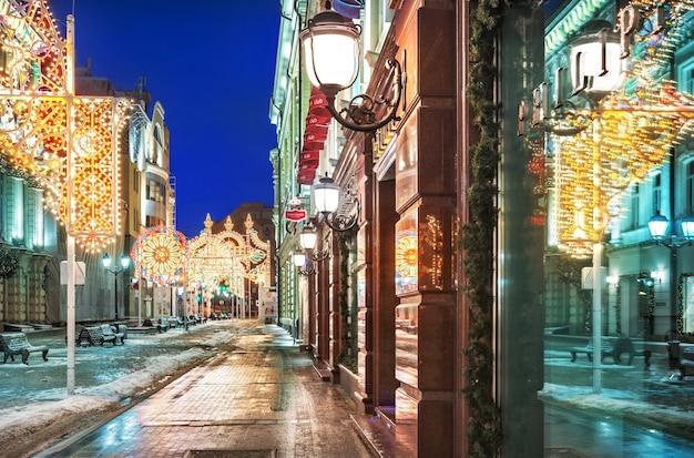 Luci e decorazioni di capodanno su nikolskaya street a mosca e lampade accese con riflessi nelle finestre