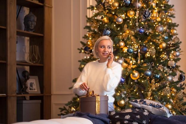 Invito alla festa di capodanno: la ragazza parla al telefono dopo aver decorato l'albero di natale, compra regali