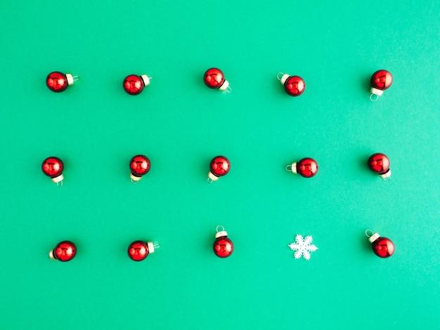 Anno nuovo pattern, layout, lay flat. molti giocattoli rossi dell'albero di natale si trovano su uno sfondo verde.