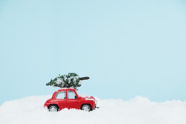 Auto rossa di capodanno con albero di natale in un paesaggio innevato