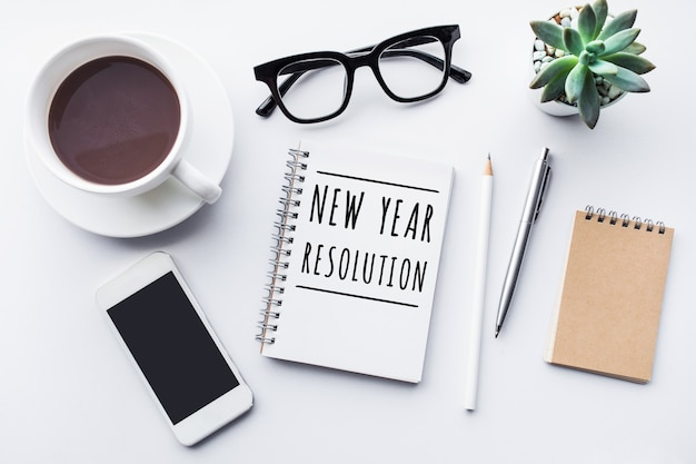 Concetti di risoluzione del nuovo anno con testo su notebook e accessori per ufficio