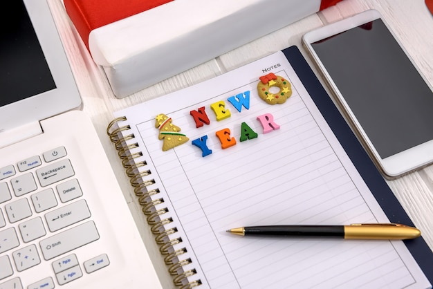 Risoluzione del nuovo anno nel blocco note con il laptop sul tavolo
