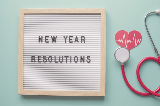 Risoluzioni per il nuovo anno sulla lavagna con cuore e stetoscopio concetto di salute e benessere