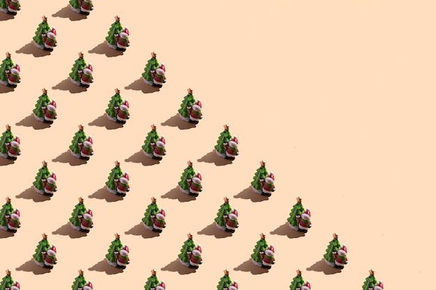 Primo piano della carta di capodanno: un pupazzo di neve con un albero di natale su uno sfondo beige con un'ombra dura. vista dall'alto con il modello senza cuciture dello spazio della copia, banner