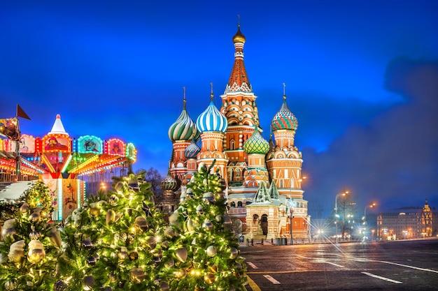 Giostra di capodanno e alberi di natale vicino alla cattedrale di san basilio sulla piazza rossa a mosca in una notte d'inverno