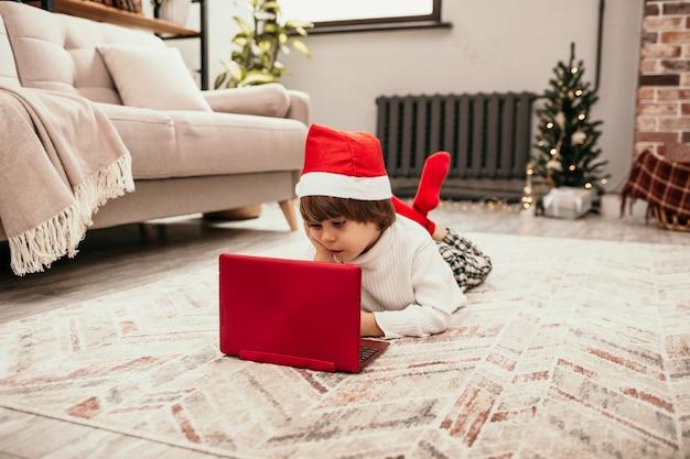 Un bambino di capodanno con un maglione bianco e un cappello rosso di natale giace sul tappeto nella stanza e guarda un laptop rosso