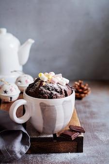 Torta al cioccolato di capodanno cotta nel forno a microonde in tazza su struttura di superficie grigia vintage