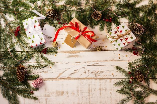 Sfondo di capodanno o natale con scatole festive, rami di abete e coni, iconfetti placcati. una copia dello spazio.