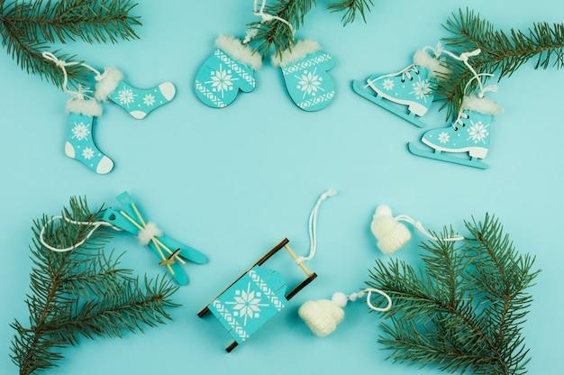 Sfondo blu di natale di capodanno con rami di abete rosso e giocattoli decorativi in legno e maglia.vista dall'alto. una copia dello spazio.