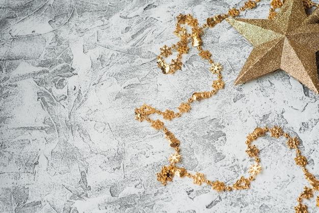 Composizione di capodanno o natale di capodanno, giocattoli dorati lucidi e stelle su uno sfondo materico luminoso. disposizione piatta, layout, cornice, posto per il testo, copia spazio, vista dall'alto