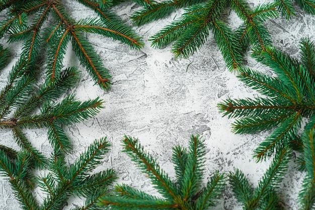 Composizione di capodanno o natale di rami verdi di abete rosso su uno sfondo luminoso. disposizione piatta, layout, cornice, posto per il testo, copia spazio, vista dall'alto