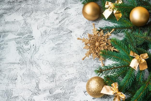 Composizione di capodanno o natale di rami verdi di abete e capodanno, giocattoli dorati lucidi e stelle su uno sfondo materico luminoso. disposizione piatta, layout, cornice, posto per il testo, copia spazio, vista dall'alto