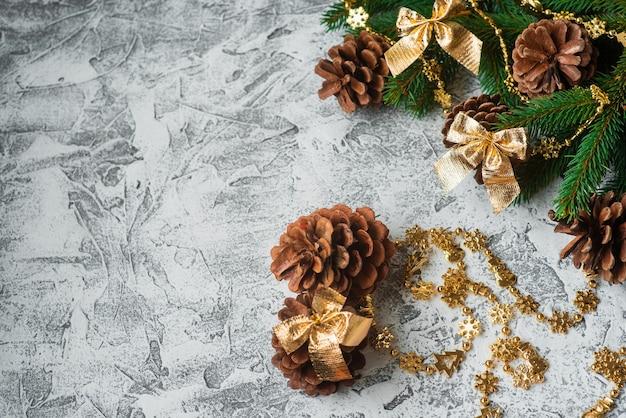Composizione di capodanno o natale di rami verdi di abete rosso, pigne e giocattoli dorati lucidi di capodanno e