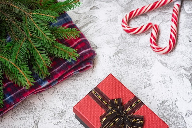 Composizione di capodanno o natale di rami verdi di abete rosso, plaid rosso, regalo e lecca-lecca di natale su uno sfondo materico luminoso. disposizione piatta, layout, cornice, spazio di copia