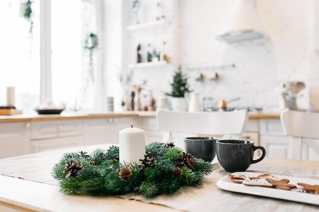 La tavola di natale di capodanno è decorata con una ghirlanda e candele, in attesa di ospiti, congratulazioni