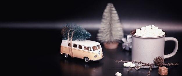 Composizione di capodanno. una tazza di cioccolata calda con marshmallow. una macchinina con un albero di natale sul tronco.