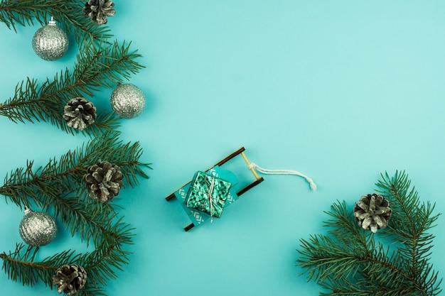 Composizione di capodanno con rami decorati di palline e coni d'argento di abete rosso. slitta decorativa con un regalo su sfondo blu. copia spazio.