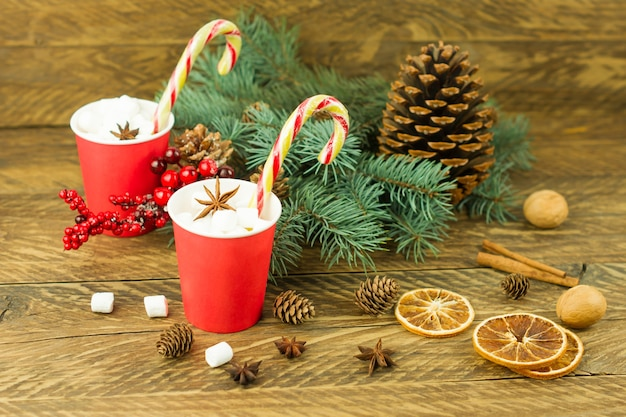 Composizione di capodanno su uno sfondo di legno. due bicchieri di carta rossa con caffè e marshmallow, caramello, rami di abete blu e un cono di cedro.